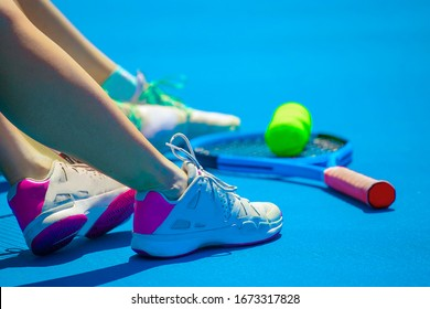 legs of a tennis player girl casting a shadow on the blue court