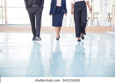Legs of three business partners walking in office. Two female colleagues and businessman going together in corridor. Business team concept