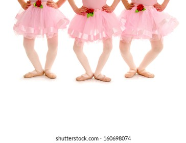 Legs of three small girls in Ballet Recital Costume and Slippers pose in Plie