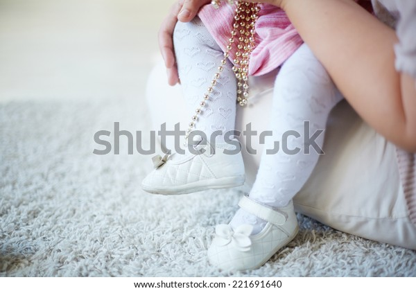 Legs of a toddler sitting on her mother�¢??s laps