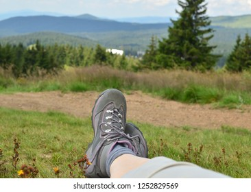 Legs in tracking shoes resting on a mountain field