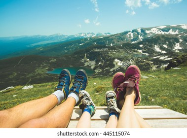 Legs of traveler family sitting on a high mountain. Freedom concept