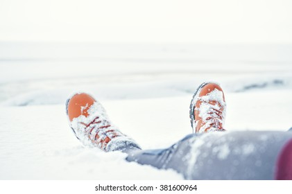 Legs of traveler sitting in deep snow outdoor. Travel and discovery concept
