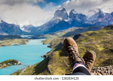 Legs of traveler sitting on a high mountain top in travel. Freedom concept. Los Cuernos rocks, Patagonia, Chile