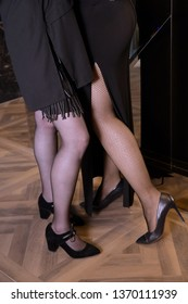Legs of two attractive girls, dressed in sexy stockings and high heels. Network stockings