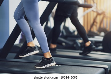 Legs of two girl friends working out on treadmill