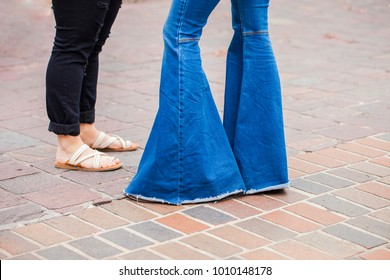 Legs of two girls, one wears seventie's style bell bottom jeans, the other one sandals and modern ripped jeans