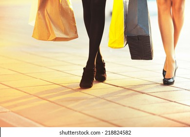 Legs of two glamorous girlfriends with paperbags. Big Sale Shopping