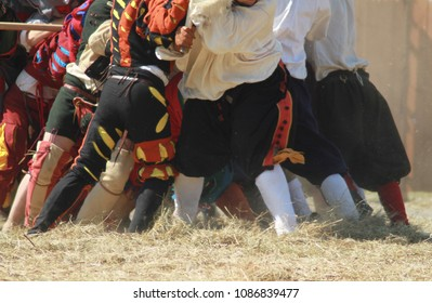 The legs of two groups of men in historical costumes. Colorful mercenaries (landsknechts) fight with peasants in poor clothes.