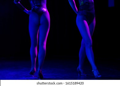 Legs of two sexy dancers in fishnet stockings. Strippers or cabaret pole dancers at a stage in a strip club or erotic striptease show.
