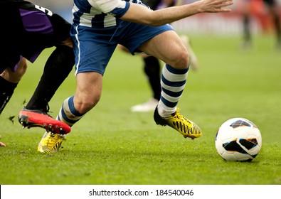 Beine von zwei Fußballspielern spielen auf einem Spiel