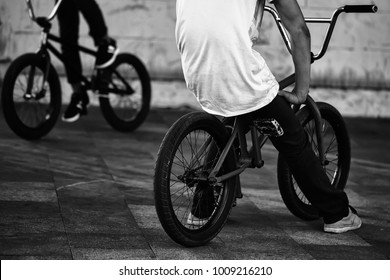 Legs of two teenager boys sitting on orange and black bmx low bicycles on street summer male sports activity outdoor closeup on natural background, horizontal picture