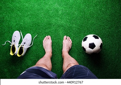 Legs of unrecognizable barefoot football player against artificial grass. Soccer ball, cleats. Studio shot on green grass. Copy space.
