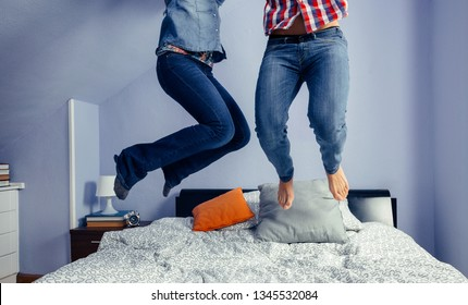 Legs of unrecognizable happy couple jumping on the bed indoors