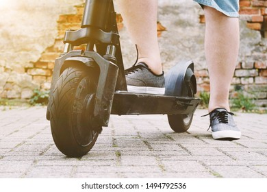 legs of unrecognizable person with electric kick scooter or e-scooter - e-mobility or micro-mobility hipster lifestyle trend concept with sun flare filter