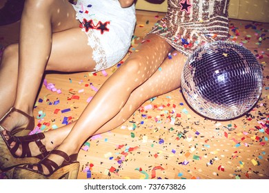 Legs of unrecognizable women sitting on floor covered with confetti during glamour party.