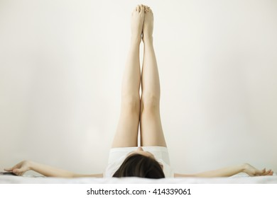 Legs up. Artistic close up of woman's legs lying on bed in bedroom