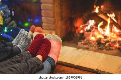 Legs view of happy family wearing warm socks in front of fireplace - Winter, love and cozy concept - Focus on pink woolen socks