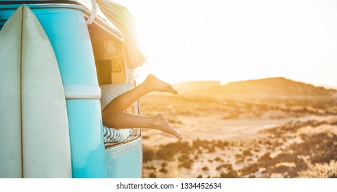 Legs view of happy surfer girl inside minivan at sunset - Young woman having fun on summer vacation - Travel,sport and nature concept - Focus on feet