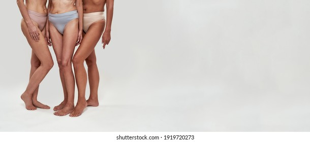 Legs and waists of women dressed in bikini staying in right corner of a studio background. Copy space