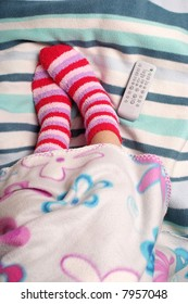 Legs, warm socks and remote control on the blanket