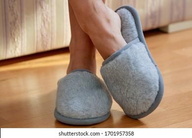 Legs wearing fluffy grey wool slippers on feet inside the livingroom