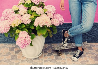 Legs wearing jeans and sneakers with mini skateboard outdoor near beautiful pink flowers