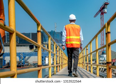 legs wearing pair of Safety shoe of worker walking in mind step on the steel checker plate in safety walkway at workplace