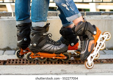 Legs wearing rollerblades. Black and orange inline skates. Improved materials and new design.