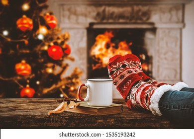 Legs in winter christmas socks on wooden top board with fireplace background in cozy home interior.