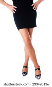 Legs of a woman in black dress, isolated on white