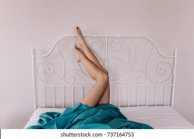 Legs of a woman with a blue sheet on a bed.