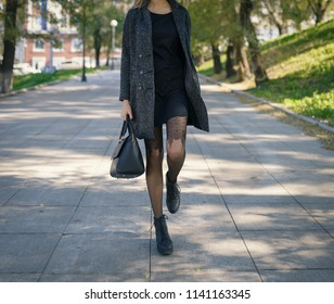 Legs of woman in coat autumn at street.