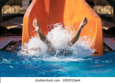 legs of a woman coming down on the inflatable ring by the slide in the aqua park. Summer Vacation. Weekend on resort