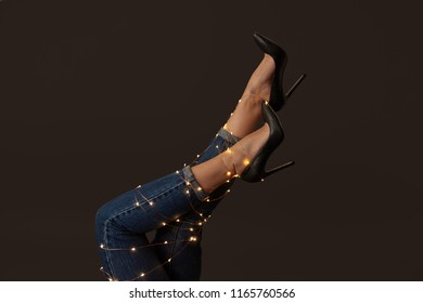 Legs of a woman in elegant black high-heeled shoes with bright christmas lights on a black background. As the layout for your ideas