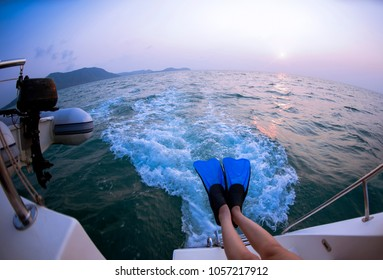 legs of woman in flippers for snorkeling in the sea, and sitting on boat view the traces left behind trail on water on yacht,enjoying their holidays.
