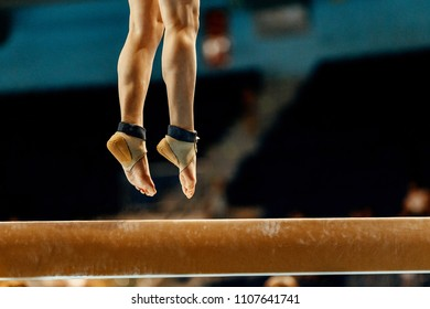 legs woman gymnast jump while exercising on balance beam