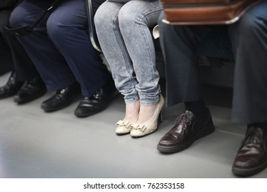 Legs of a woman in jeans, sitting in a subway car among men