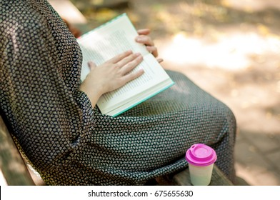 Legs of a woman in long dress, on a bench in the park. Girl reading a book in a park outdoors with cup of coffee. Close-up. Point of view. Reading a book and drinking coffee, outdoors.
