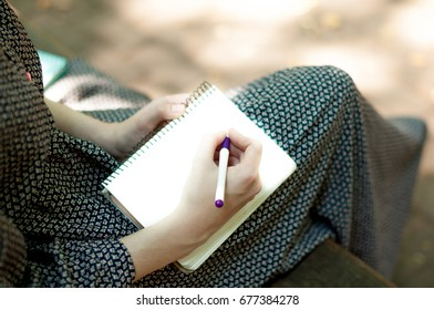 Legs of a  woman in long dress, on a bench in the park. Girl Write notes to notepad in a park outdoors Close-up. Point of view.