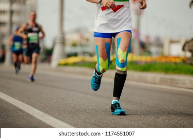 legs woman runner in compression socks and kinesio tape on knees