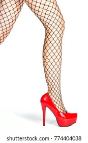 legs of a woman in shiny red platform high heels shoes and fishnet stockings