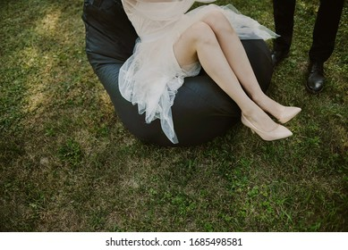 legs of a woman sitting on a puff on the grass, next to the legs of a standing man