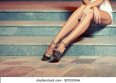 Legs of woman sitting on stairs. Toned image instagram style color