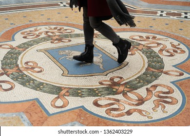 Legs of a woman spinning on the bull mosaic for making a wish in Milan Italy