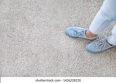 Legs of woman standing on soft carpet, top view
