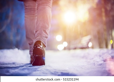 Legs of woman walking in winter park evening. Girl boots walking snow weather. Closeup of winter shoes. Blurred lens flare background with copy space area for a text.