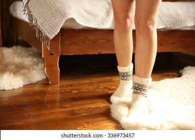 Legs of woman in warm socks on white carpet on wooden background