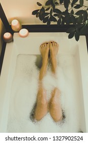 Legs of woman in the water of the bathtub, girl relaxes immersed in a bath. Relaxing candles atmosphere. Rest and cool down after work, moment for oneself View from above, meditation in a domestic spa