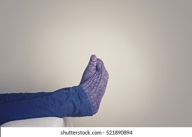 Legs with woolen socks. Man resting on sofa at home.